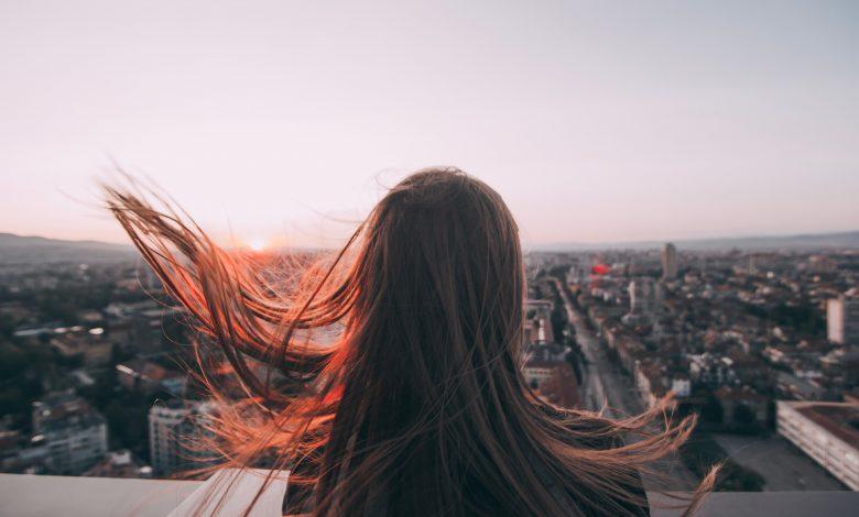 Жена, гледаща града от покрив3а на висока сграда